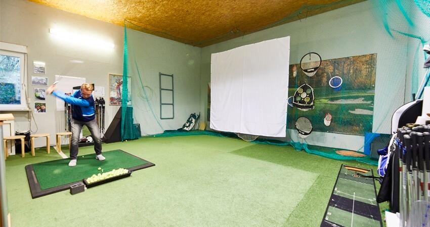 Computergestütztes Golftraining im Indoor-Trainingscenter mit Simulatoren.